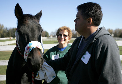 Monica Maschak - mmaschak@shawmedia.com Bob Lumber, of the City of McHenry Police Department, ties a make-shift harness onto a horse in a training session for first responders in Woodstock on Saturday.  The session taught its participants how to handle horses in the event of an emergency.