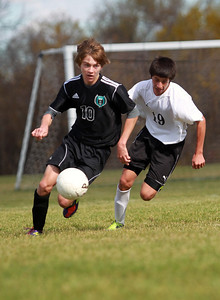Sarah Nader - snader@shawmedia.com Woodstock North's Aaron Jones (left) and Harvard's Pedro Guzman chase after the ball during Saturday's Regional Final on October 20, 2012 in Harvard. Harvard won, 2-0.