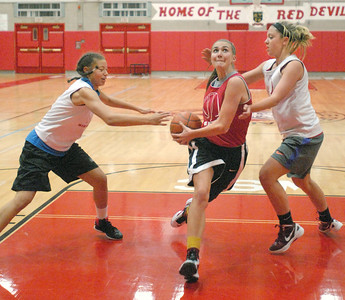 Gabrielle Rush drives to the basket, splitting Alecia Gulledge (left) and Lauren Zapka on Wednesday, Oct. 31, 2012, at Hinsdale Central girls basketball practice. Practices started this week. Staff photo by Bill Ackerman
