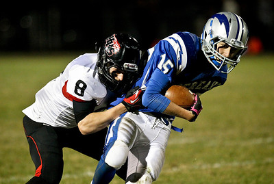 Josh Peckler - Jpeckler@shawmedia.com Woodstock's Mitch Kohley (15) tries to break away from Huntley's Tyler Schwartz during the first quarter at Woodstock High School Friday, October 12, 2012.