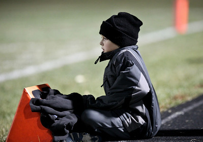 Josh Peckler - Jpeckler@shawmedia.com Sean Ryan, 8 tries to keep warm as he watches Woodstock play Huntley from the 20 yard line at Woodstock High School Friday, October 12, 2012.