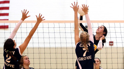 Mike Greene - mgreene@shawmedia.com Jacobs' Katie Mahoney hits the ball as Cary-Grove's Alex Larsen (left) and Morgan Lee defend during a match Thursday, October 4, 2012 at Jacobs High School in Algonquin. Jacobs (16-5) defeated Cary-Grove (12-12) in straight sets 25-17, 25-23.