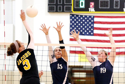 Mike Greene - mgreene@shawmedia.com Jacobs' Alyssa Ehrhardt (left) swings to spike the ball as Cary-Grove's Sam Katchen and Mallory Wilczynski attempt to defend during a match Thursday, October 4, 2012 at Jacobs High School in Algonquin. Jacobs (16-5) defeated Cary-Grove (12-12) in straight sets 25-17, 25-23.
