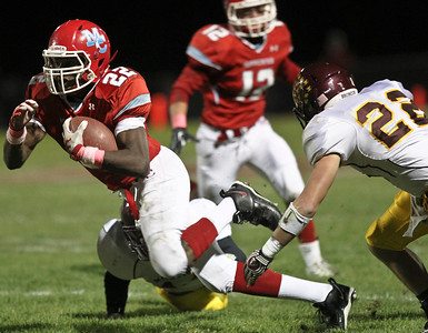Josh Peckler - Jpeckler@shawmedia.com Marian Central's Ephraim Lee tries to gain some extra yards after being hit by Montini defenders during the first quarter at Marian Central High School Friday, October 5, 2012. Marian Central won the game 49-24.