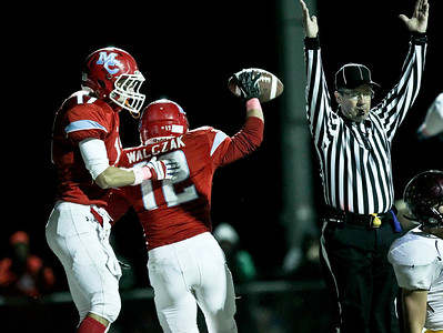 Josh Peckler - Jpeckler@shawmedia.com Marian Central's Greg Wolczak (12) celebrates with teammate Brett Olson after he scored a touch down in the first quarter against Montini at Marian Central High School Friday, October 5, 2012. Marian Central won the game 49-24.