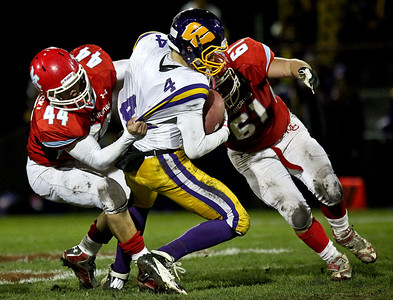 Josh Peckler - Jpeckler@shawmedia.com Marian Central's Thomas Lesniewski (44) and Josh Olsen (61) sack Wauconda quarterback Austin Swenson during the first quarter at Marian Central High School Friday, October 26, 2012. Marian Central defeated Wauconda 42-10 in a IHSA 5A first round playoff game.