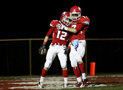 Josh Peckler - Jpeckler@shawmedia.com Marian Central's Greg Walczak (12) is congratulated by teammate Breet Olson after Walczak caught a touchdown pass during the second quarter against Wauconda at Marian Central High School Friday, October 26, 2012. Marian Central defeated Wauconda 42-10 in a IHSA 5A first round playoff game.