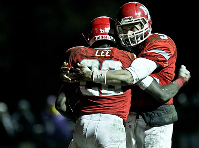 Josh Peckler - Jpeckler@shawmedia.com Marian Central's Ephraim Lee is hugged by Chris Streveler after Lee scored on a touchdown run during the third quarter against Wauconda at Marian Central High School Friday, October 26, 2012. Marian Central defeated Wauconda 42-10 in a IHSA 5A first round playoff game.