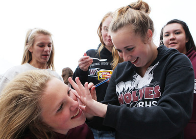 Mike Greene - mgreene@shawmedia.com Freshman Kira Brandt (left), 15, has her face painted by classmate Beth Houte, 14, during a homecoming block party Friday, October 5, 2012 at Prairie Ridge High School in Crystal Lake. Homecoming festivities capped off with a home football game against Jacobs Friday night. Jacobs defeated the Wolves 34-16.