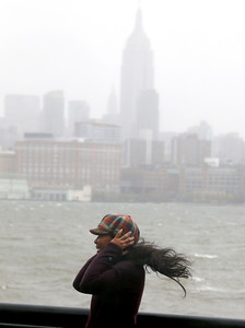A woman covers her ears while posing for a photograph as her hair blows in the wind at the waterfront in Hoboken, N.J., as the Hudson River begins to rise and flood the area with the arrival of Hurricane Sandy, Monday, Oct. 29, 2012. Hurricane Sandy continued on its path Monday, as the storm forced the shutdown of mass transit, schools and financial markets, sending coastal residents fleeing, and threatening a dangerous mix of high winds and soaking rain.   (AP Photo/Julio Cortez)