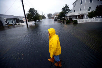Al Daisey walks in the flood water in front of his home as Hurricane Sandy bears down on the East Coast, Monday, Oct. 29, 2012, in Fenwick Island, Del.  Hurricane Sandy continued on its path Monday, as the storm forced the shutdown of mass transit, schools and financial markets, sending coastal residents fleeing, and threatening a dangerous mix of high winds and soaking rain.  (AP Photo/Alex Brandon)