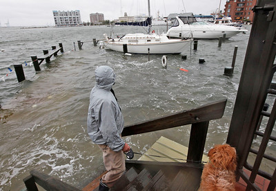 Norfolk resident Jack Devnew and his dog check on his boat at a marina near downtown Norfolk, Va., Monday, Oct. 29, 2012. Rain and wind from Hurricane Sandy are hitting the area. (AP Photo/Steve Helber)