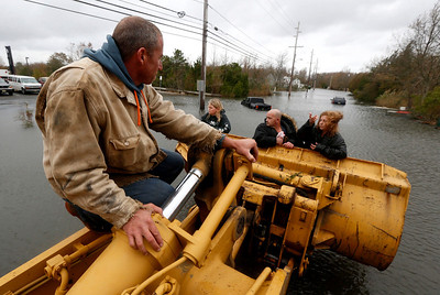 Brian Hajeski, 41, left, rides on the extension of a front loader as he helps neighbors get out of their flooded home and into dry land the morning after superstorm Sandy rolled through, Tuesday, Oct. 30, 2012, in Brick, N.J. Sandy, the storm that made landfall Monday, caused multiple fatalities, halted mass transit and cut power to more than 6 million homes and businesses. (AP Photo/Julio Cortez)