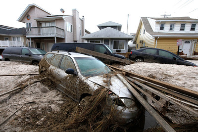 A car lies buried in sand and debris in the aftermath of superstorm Sandy, Tuesday, Oct. 30, 2012, in Long Beach, N.Y.  Sandy, the storm that made landfall Monday, caused multiple fatalities, halted mass transit and cut power to more than 6 million homes and businesses.(AP Photo/Jason DeCrow)