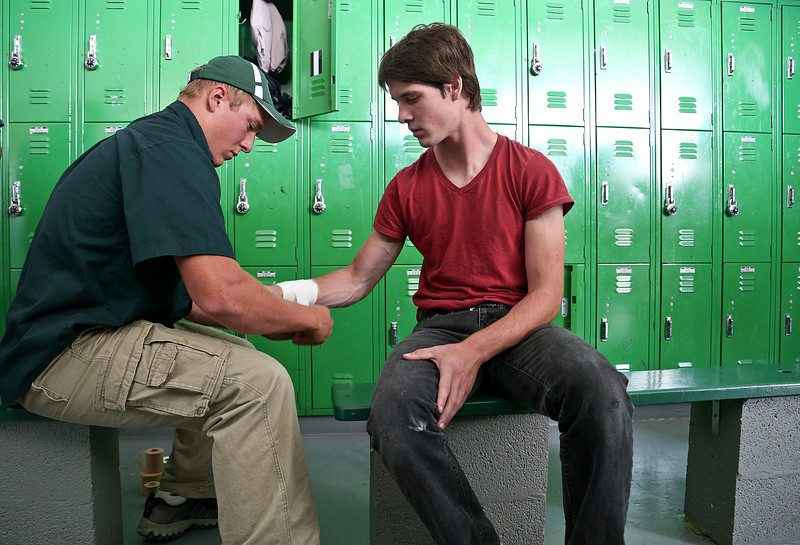 Josh Peckler - Jpeckler@shawmedia.com Alden-Hebron's Jaritt Cornett (right) has his wrist taped by assistant coach Dean Beck inside the locker room before playing Marquette Academy at Alden-Hebron High School Saturday, September 29, 2012.