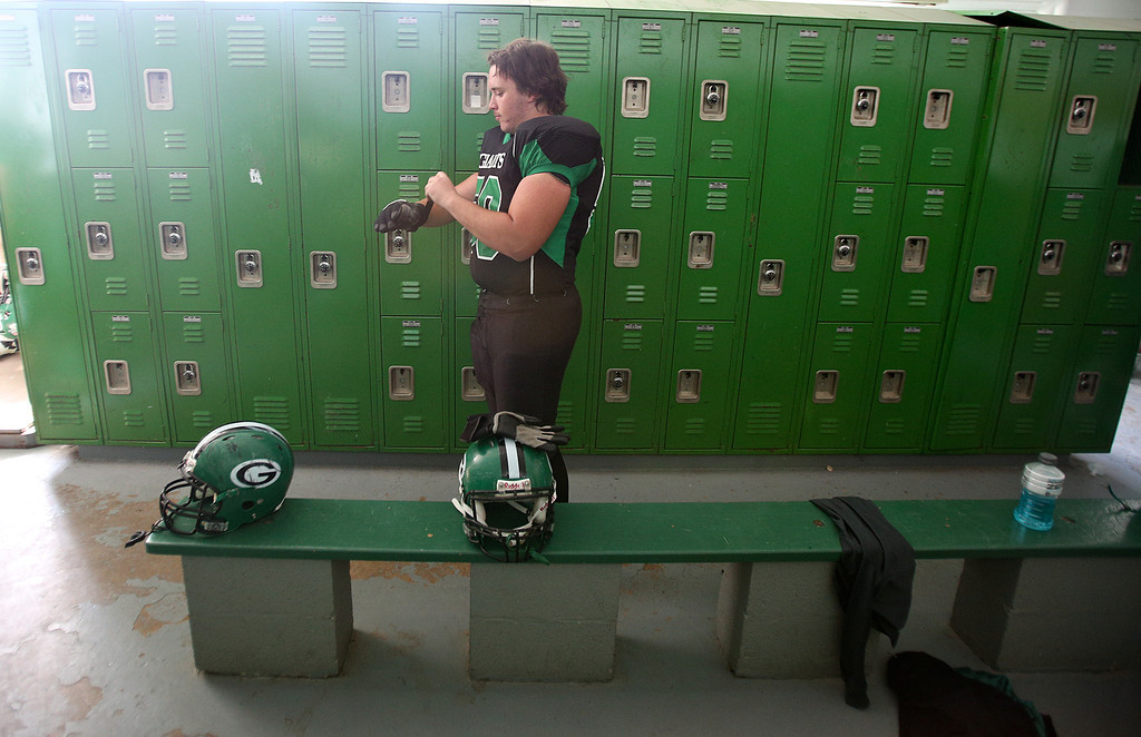 Josh Peckler - Jpeckler@shawmedia.com Alden-Hebron's Anthony Rajkowski puts on gloves inside the locker room before playing Marquette Academy at Alden-Hebron High School Saturday, September 29, 2012.