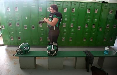 Josh Peckler - Jpeckler@shawmedia.com Alden-Hebron's Anthony Rajkowski puts on gloves inside the locker room before playing Marquette Academy at Alden-Hebron High School Saturday, September 29, 2012.