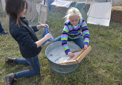 Monica Maschak - mmaschak@shawmedia.com Mya Ruse, 10, and Abigail Olsson, 9, of Algonquin wash clothes at the Trail of History at Glacial Park on Saturday.  Activities gave young attendees a taste of what chores were like in the early settler days.