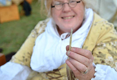 Monica Maschak - mmaschak@shawmedia.com Joyce Krauz, of the Celtic Education of Living Theater Society, holds up the carved tip of a feather at the Trail of History in Glacial Park on Saturday.  Krauz demonstrated how to make a feather into a pen.  Attendees witnessed what life was like in the Northwest Territory from 1670 to 1850.  The re-enactment featured more than 200 interpreters from across the country who demonstrate the crafts and trades from early settler days.