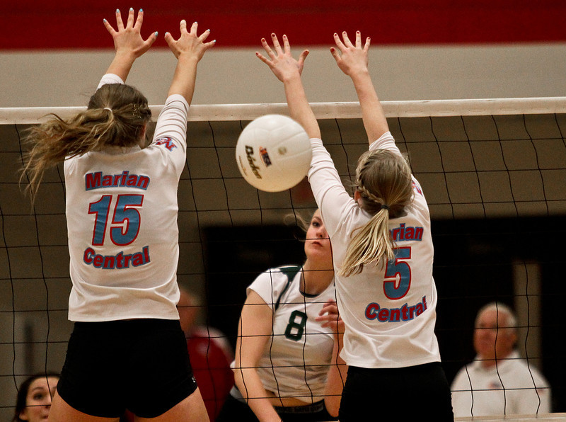 Josh Peckler - Jpeckler@shawmedia.com Grayslake Central's Alex Dahlstrom (8) hits the ball in between Marian Central blockers Shannon Wuensch (15) and Alex Kaufmann during the second set at Marian Central High School Tuesday, October 30, 2012.