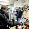 Colleen Quinn (left) of Geneva uses her finger to sign for a credit card purchase with the help of employee Sharon Booth at Perk Up! Geneva coffee shop, located at the Geneva Metra station. The shop uses an iPad and a Square credit card reader to ring up purchases.Members of the Batavia business community attend a ribbon-cutting ceremony for the office of dentist Ronald A. Murphy on Thursday, Oct. 18 at 1605 W. Wilson St.