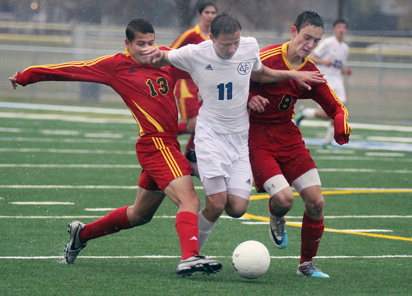 Jeff Krage – For the Kane County Chronicle<br /> Geneva's Beck Nebergall splits Batavia defender's Peter Munson, left, and Brendan Allen during Saturday's IHSA 3A regional quarterfinal at Geneva High School.<br /> Geneva 10/13/12