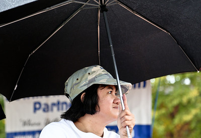 Josh Peckler - Jpeckler@shawmedia.com Anne Tolosa of Kenosha, Wisc. sits under a umbrella as it rains during the The Old Time Country Harvest Festival in Algonquin Saturday, October 13, 2012. Due to rain very few people came out to enjoy the events Saturday.