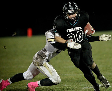 Josh Peckler - Jpeckler@shawmedia.com Woodstock North's Grant Wade runs with the ball while Grayslake North's Jake Smith tries to bring him down during the first quarter at Woodstock North High School Friday, October 19, 2012.
