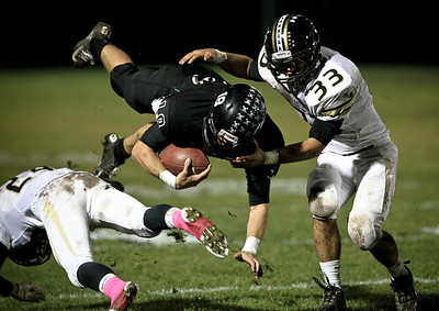 Josh Peckler - Jpeckler@shawmedia.com Woodstock North quarterback Brian Loftin (18) dives in the air while Grayslake North's Zach Juron (33) tries to bring him down during the second quarter at Woodstock North High School Friday, October 19, 2012.