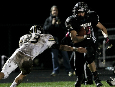Josh Peckler - Jpeckler@shawmedia.com Woodstock North's Adam Haimbaugh runs with the ball while while Grayslake North's Zach Juron attempts to tackle him during the first quarter at Woodstock North High School Friday, October 19, 2012.