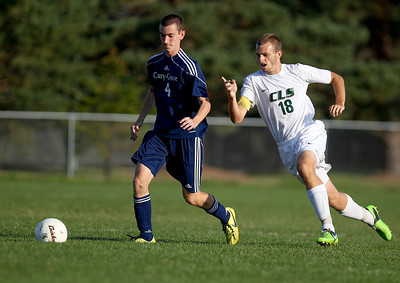 Sarah Nader- snader@shawmedia.com Cary-Grove's Brad Sigsworth (left) and Crystal Lake South's Gary Sexson run after the ball during the first half of Tuesday's soccer match in Crystal Lake October 1, 2013.