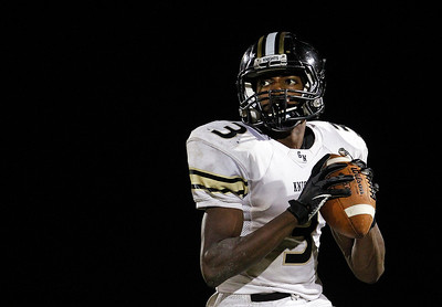 Kyle Grillot - kgrillot@shawmedia.com   Grayslake North junior Titus Booker looks to pass the ball during the fourth quarter of the high school football game against Grayslake North Friday, October 4, 2013.
