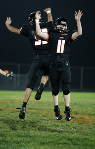Kyle Grillot - kgrillot@shawmedia.com   Cyrstal Lake Central junior Matt Decoste (11) and junior Jose Figueroa celebrate after the final play of the high school football game against Grayslake North Friday, October 4, 2013.