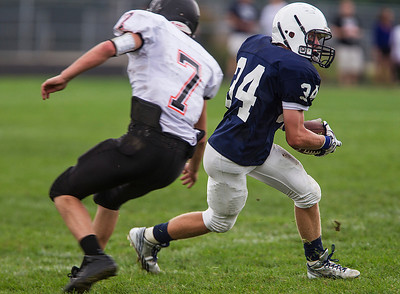Kyle Grillot - kgrillot@shawmedia.com   Cary-Grove junior George Hartke (34) runs the ball under the defense of McHenry Troy McClaughry (7) during the second quarter of the high school football game Saturday, October 5, 2013.