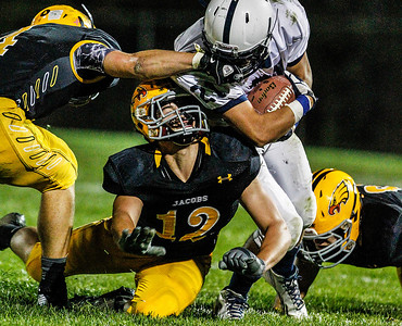 Kyle Grillot - kgrillot@shawmedia.com   Jacobs sophomore Brenden Heiss (12) gets pinned between senior Tommy Savage's tackle on Cary-Grove junior Zach McQuade during the third quarter of the high school football game against Cary-Grove Friday October 11, 2013. Jacobs won the game 36-35.