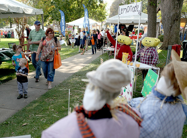 Onlookers view some of the scarecrows on display during Scarecrow Fest in downtown St. Charles Friday afternoon.