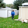 Rover Rescue foster home coordinator Teri Grandt walks in the backyard of her North Aurora home with one of her foster dogs, Dharma.