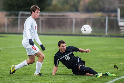 Kyle Grillot - kgrillot@shawmedia.com   Prairie Ridge junior Sam Click (16) slides to pass the ball upfield under the defense of Marian Central junior Connor Hull during the second half of the in Class 2A regional semifinal match at Marian Central High School Tuesday, October 22, 2013. Marian Central won the match 3-1.