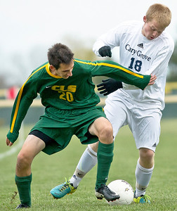 Brett Moist/ for the Northwest Herald  Crystal Lake South's Andrew Perrine fights for the ball with Cary Grove's Danny Kinnerk during the 1st half of their Regional Semi final match at Crystal Lake South on Wednesday. Crystal Lake South defeated Cary Grove 3-2 in Overtime.