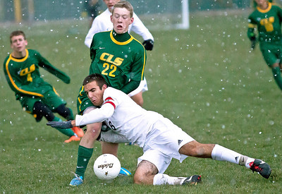 Brett Moist/ for the Northwest Herald  Cary Grove's Tyler Szydlo dives into Crystal Lake South's Andrew Grabowski in attempt to kick the ball during the 2nd over time period of their Regional Semi final match at Crystal Lake South on Wednesday. Crystal Lake South defeated Cary Grove 3-2 in Overtime.