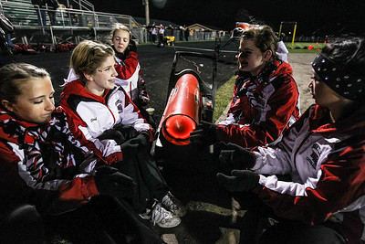 Sarah Nader- snader@shawmedia.com Huntley cheerleaders warm up by the heater during half time of Friday's football at Crystal Lake South October 25, 2013.