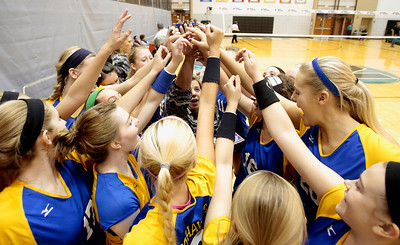 Kyle Grillot - kgrillot@shawmedia.com   The Johnsburg team comes together around coach Sue Feely (center) for a cheer before the start of the second game of the regional semifinal match against Woodstock.