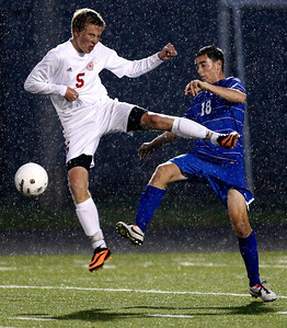 Kyle Grillot - kgrillot@shawmedia.com  Marian Central junior Beau Meintz (5) flies through the air while attempting to gain control of the ball from Vernon Hills junior Brad Burrows (18) during the second half of the class 2A boys soccer semifinal match between Marian Central and Vernon Hills Wednesday, October 30, 2013.  Vernon Hills won the match 10-0.