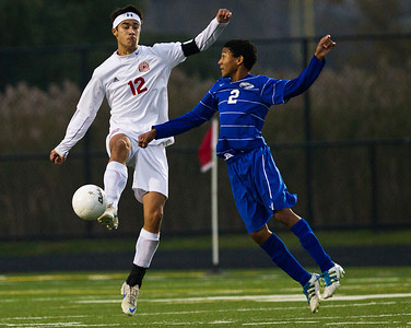 Kyle Grillot - kgrillot@shawmedia.com  Vernon Hills senior Caleb Shaw (2) jumps to try to stop Marian Central junior Jordan Peterson from passingthe ball during the class 2A boys soccer semifinal match between Marian Central and Vernon Hills Wednesday, October 30, 2013. Vernon Hills won the match 10-0.