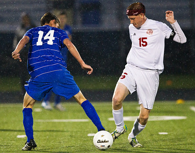 Kyle Grillot - kgrillot@shawmedia.com  Vernon Hills senior David White (14) and Marian Central senior Riley Blaz fight for control of the ball during the class 2A boys soccer semifinal match between Marian Central and Vernon Hills Wednesday, October 30, 2013.  Vernon Hills won the match 10-0.