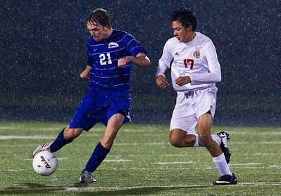 Kyle Grillot - kgrillot@shawmedia.com  Marian Central sophomore Fermado Tapia tries to stop Vernon Hills senior Nick Bryson (21) from passing the ball during the class 2A boys soccer semifinal match between Marian Central and Vernon Hills Wednesday, October 30, 2013. Vernon Hills won the match 10-0.