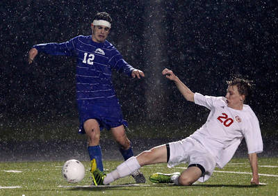 Kyle Grillot - kgrillot@shawmedia.com   Marian Central sophomore Bryan Hart (20) slides to attempt to gain control of the ball from Vernon Hills senior Jeremy Cohen during the second half of the class 2A boys soccer semifinal match between Marian Central and Vernon Hills Wednesday, October 30, 2013.  Vernon Hills won the match 10-0.