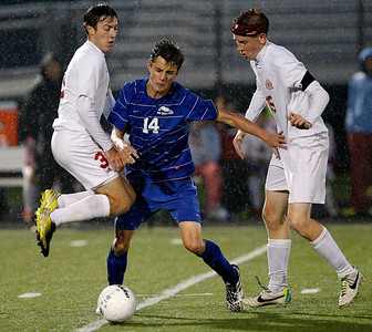 Kyle Grillot - kgrillot@shawmedia.com  Vernon Hills senior David White (14) fights through Marian Central junior Connor Hull (left) and senior Riley Blaz during the class 2A boys soccer semifinal match between Marian Central and Vernon Hills Wednesday, October 30, 2013. Vernon Hills won the match 10-0.