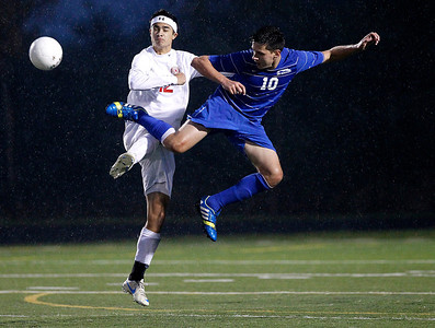 Kyle Grillot - kgrillot@shawmedia.com  Vernon Hills junior Ilya Kravtsev (10)jumps to kick the ball away from Marian Central junior Jordan Peterson(12) during the class 2A boys soccer semifinal match between Marian Central and Vernon Hills Wednesday, October 30, 2013. Vernon Hills won the match 10-0.