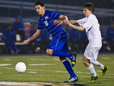 Kyle Grillot - kgrillot@shawmedia.com  Marian  Central sophomore Bryan Hart tries to hold Vernon Hills junior Ilya Kravtsev (10) as he passes the ball during the class 2A boys soccer semifinal match between Marian Central and Vernon Hills Wednesday, October 30, 2013. Vernon Hills won the match 10-0.